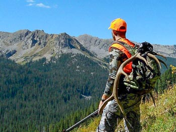 a hunter in the mountains with antlers strapped to his pack
